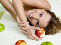 Woman lying on bed with apples, smiling